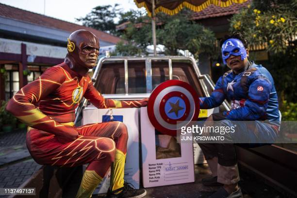 Indonesian election commission workers wearing superhero costumes deliver ballot boxes for the upcoming general elections in Surabaya East Java on...