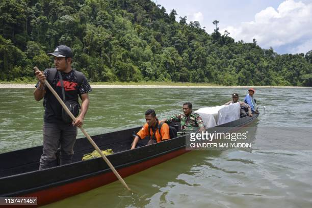 Indonesian election officials transport ballot boxes to a remote village by boat along a river in Manggamat Southern Aceh province on April 16 on the...