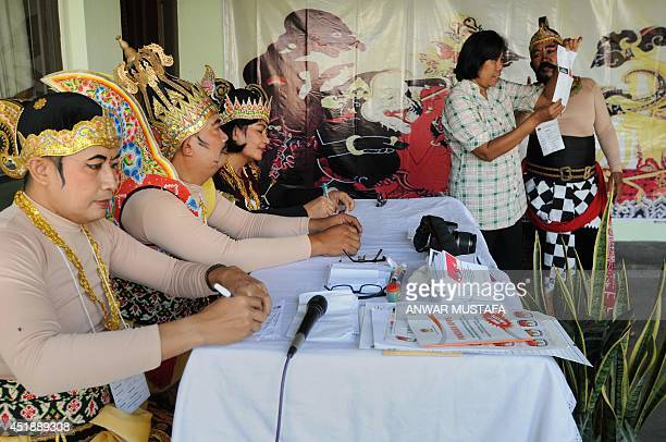 Indonesian election officials wearing Javanese wayang costumes assist voters in Solo in central Java island on July 9 2014 Jakarta governor Joko...