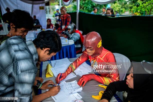 TOPSHOT Indonesian election workers dressed in superhero costumes register voters at a polling station in Surabaya on April 17 2019 Indonesia kicked...