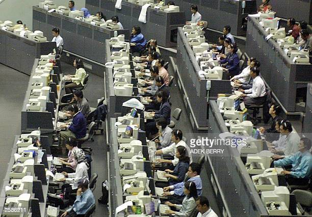 Indonesian employees of Jakarta Stock Exchange work on during a morning session in Jakarta 25 September 2003 Shares are expected to continue to rise...