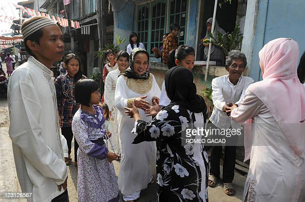 Indonesian families greet each other during a visit to relatives' houses in Jakarta to celebrate EidalFitr on August 31 2011 The world's most...