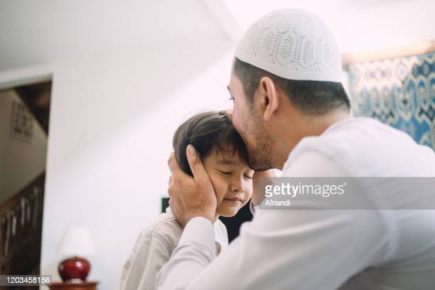indonesian family celebrating eid al-fitr and asking for forgiveness - eid mubarak stock pictures, royalty-free photos & images