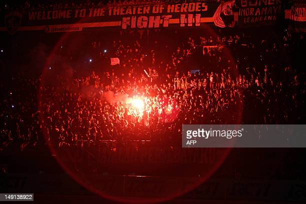 Indonesian fans light flares during the Queens Park Rangers friendly football match against Indonesian team Persebaya as part of the Queens Park...