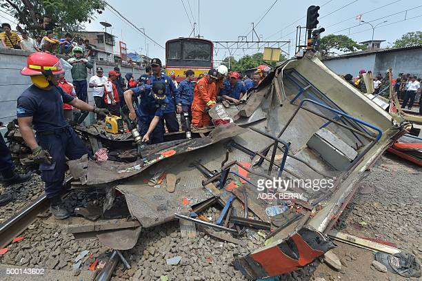Indonesian firefighters cut the wreckage of a minibus after it collided with a train in Jakarta on December 6 2015 A collision between a commuter...