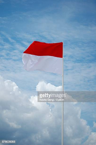 indonesian flag flying against sky - indonesia flag stock photos and pictures
