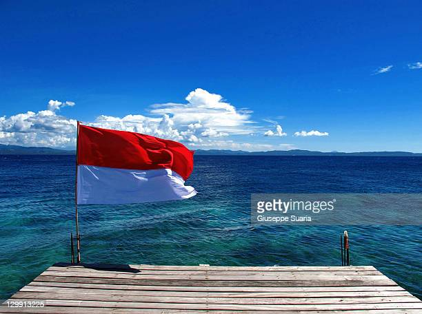 indonesian flag flying on jetty - indonesia flag stock photos and pictures