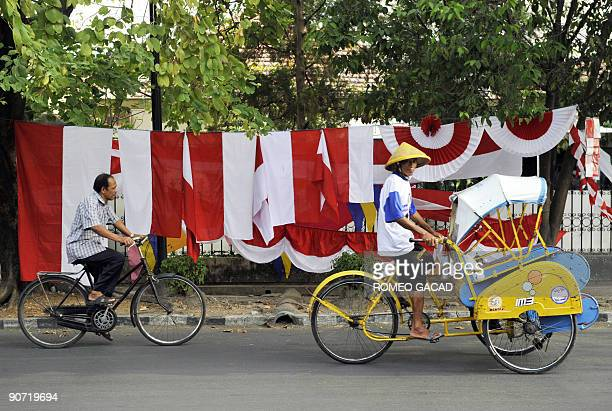 Indonesian flags are displayed on a sidewalk while cyclists pass by in Solo in Central Java on August 11 2009 as the country prepares to celebrate...