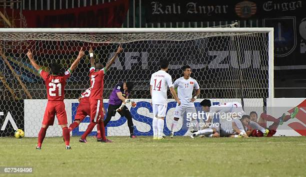 Indonesian football players celebrate a goal by Hansamu Yama Pranata after he headed the ball into the Vietnamese goal during the semi-final AFF...