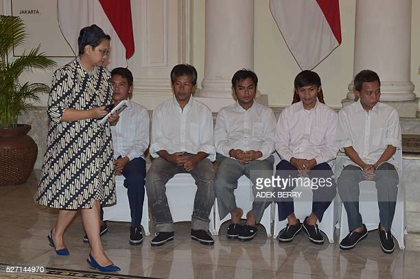Indonesian Foreign Minister Retno Marsudi walks past Indonesian sailors during a ceremony to mark the handover of hostages to their families at the...