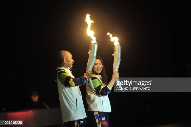 Indonesian former tennis player Yustedjo Tarik carries the flame from Indonesia and Indonesian former badminton player Susi Susanti carries the...