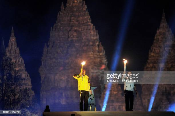 Indonesian former tennis player Yustedjo Tarik carries the flame from Indonesia and Indonesian former badminton player Susi Susanti carries the flame...