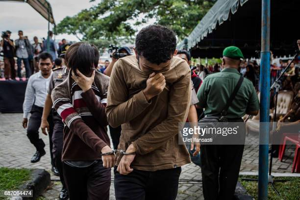 Indonesian gay couple walk as arrive for caning in public from an executor known as 'algojo' for having gay sex which is against Sharia law at...