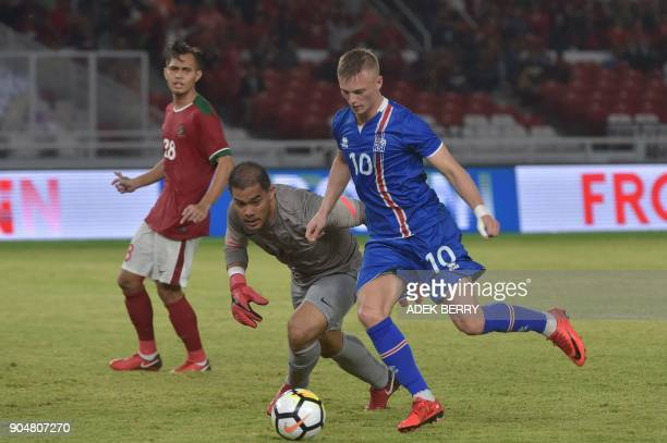 Indonesian goal keeper Andritany Ardhiyasa vies for a ball as Albert Gudmundsson of Iceland kicks for a goal during a friendly match in Jakarta on...