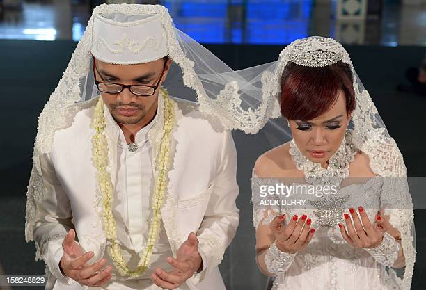 Indonesian groom Adam Afiezan and bride Sitta Kusuma pray during their Muslim wedding ceremony at a mosque in Jakarta on December 12 2012 Thousands...