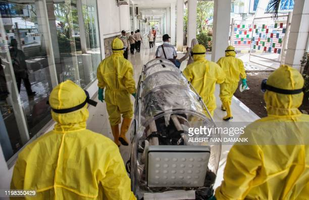 Indonesian health officials conduct an exercise drill in transporting a patient requiring isolation at the Belawan port in Medan on February 3, 2020....