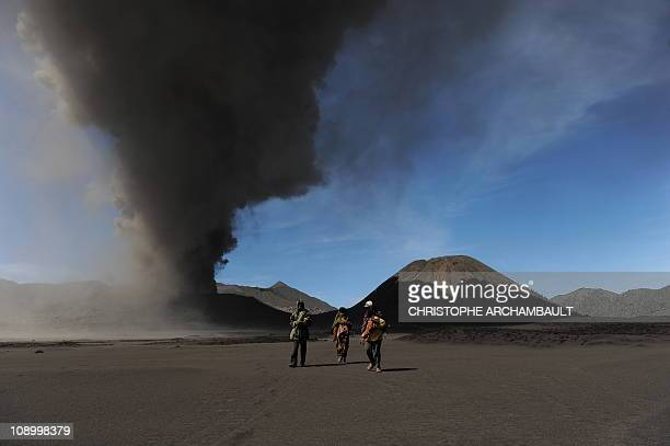 Indonesian Hindu devotees walk back from the ashshooting Mount Bromo volcano after making offerings at a temple located at its foot outside the...