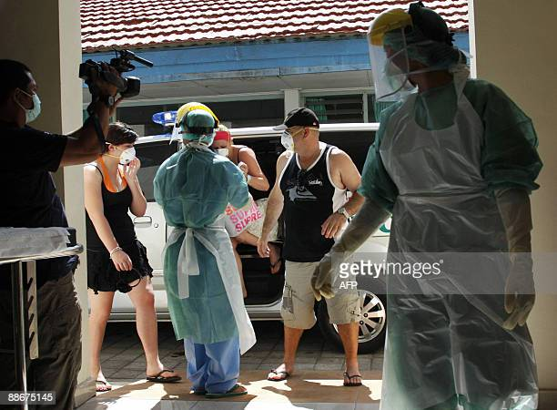 Indonesian hospital staff wearing protective suits escort three Australian tourists suffering from flulike symptoms as they arrive at the Sanglah...