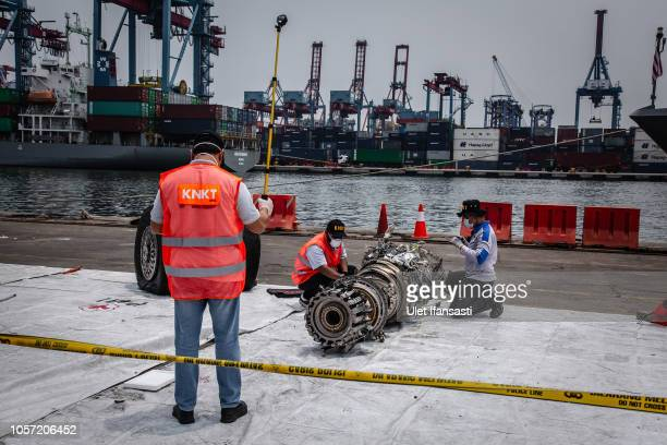 Indonesian investigators inspect the wreckage of an engine from Lion Air Flight JT 610 recovered from the sea at the Tanjung Priok port on November 4...