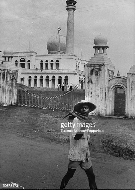 Indonesian laborer walking past the front gate of a beautiful mosque in the city