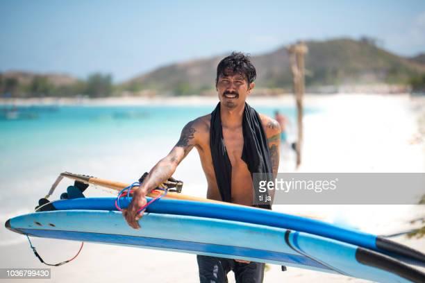 hombre indonesio llevar tablas de surf en la playa - lombok fotografías e imágenes de stock