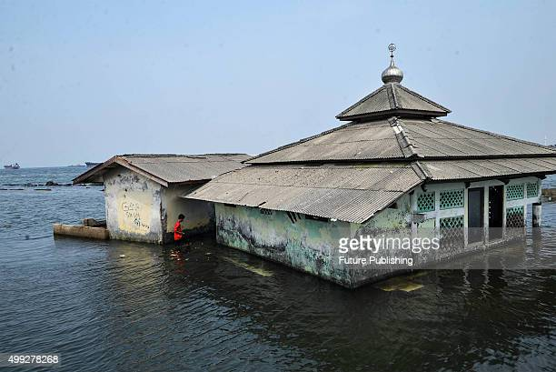 Indonesian man cross the sea water an abandoned mosque which has been surrounded by the encroaching sea sits in the Maura Baru district seen on...