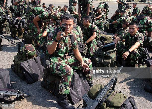 Indonesian marines check their fire arms and equipment as they wait to leave his base for conflict province Aceh with hundreds of troops in south...