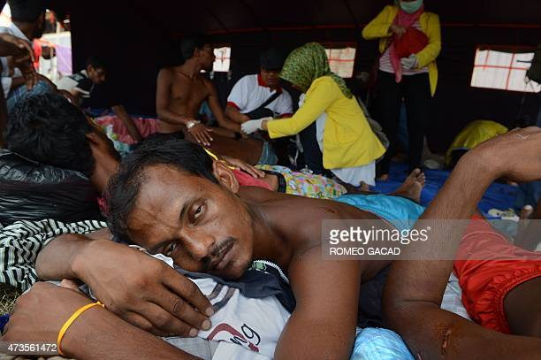 Indonesian medical personnel attend to Bangladeshi migrants some with wounds in the new confinement area in the fishing town of Kuala Langsa in Aceh...