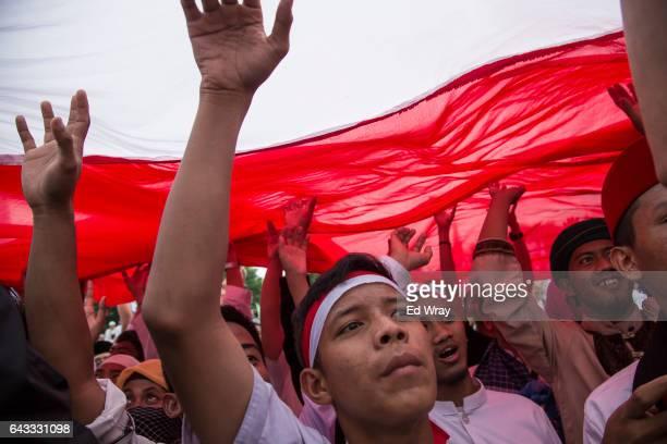 Indonesian members of hardline Islamic groups pass an Indonesian flag overhead during a demonstration against Jakarta Governor Basuki Tjahaja Purnama...