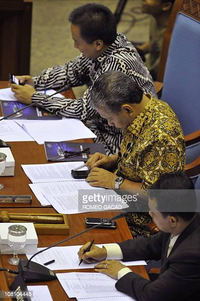 Indonesian members of parliament Agus Gumiwang Hayano Isman and Mahfudz Siddiq chairman of committee I holds their Blackberry smartphones during...