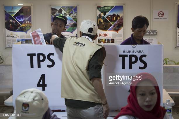 Indonesian men are seen at the polling centre during the early overseas voting at the Embassy of The Republic of Indonesia prior to the country's...