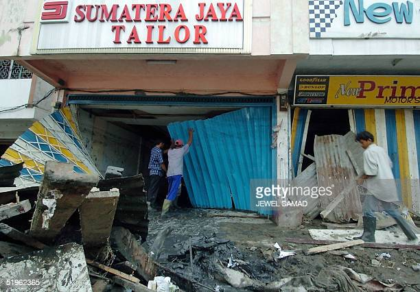 Indonesian men clean their shop devastated by tsunami in Banda Aceh 14 January 2005 The United Nations urged Indonesia not to impose a deadline on...