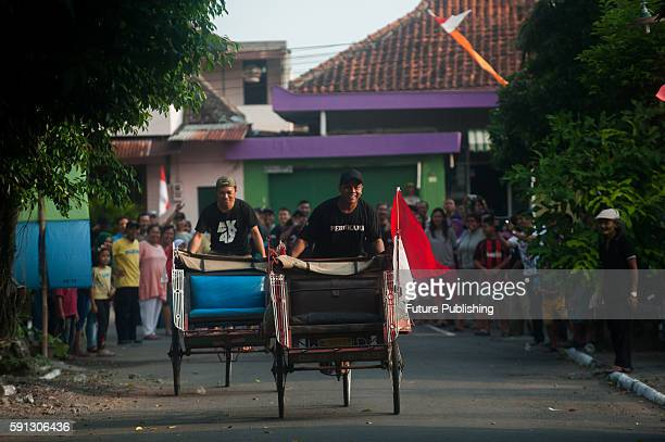 Indonesian men compete for prize in pedicab racing during the 71th National Independence Day celebrations on August 17 2016 in Yogyakarta Indonesia...