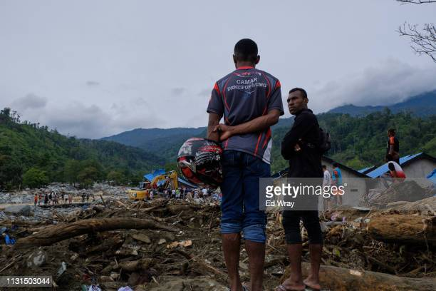 Indonesian men look out over a housing development which was largely destroyed by the recent flash floods on March 19 2019 in Sentani Papua province...