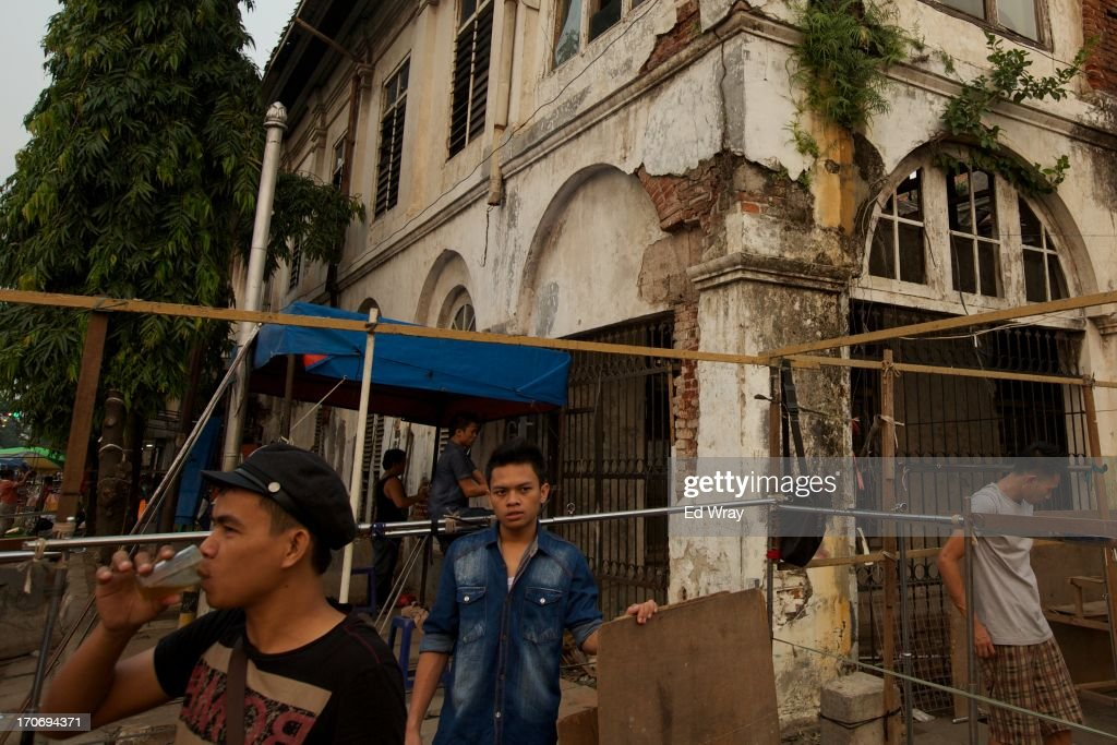 Indonesian men prepare to put up a temporary market stall in front of one of the many crumbling buildings in Kota Tua Sunday June 16, 2013 in Jakarta, Indonesia. Once known as the 'Queen of the East', Kota Tua, which means Old Town in Indonesian, is the original city of Jakarta built by the Dutch in the 16th century and called Batavia at that time. Currently, Kota Tua's beautiful Colonial architecture is in ruins, abandoned as the city edged farther south over the years. Jakarta's Governor, Joko Widodo, hopes to make it a priority to restore the old town and develop it into a high end tourist destination..