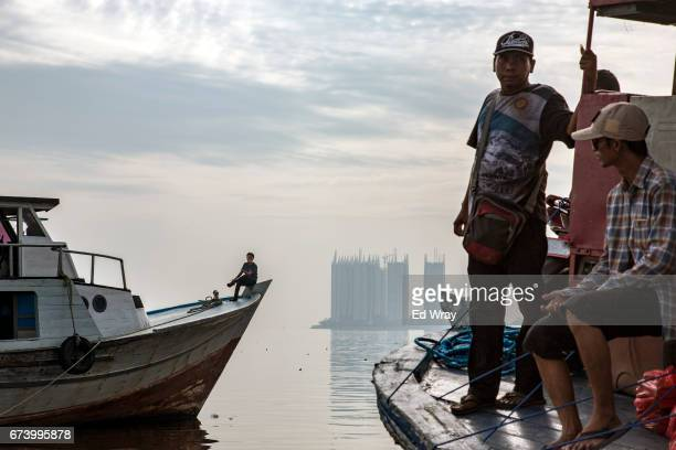 Indonesian men sit on ferries near a new apartment complex built on a narrow spit of land in the rapidly sinking northern coast of the city on April...