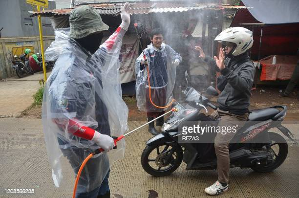 Indonesian men spray disinfectant on a motorist as he enters a neighborhood amid COVID19 coronavirus outbreak in Bekasi on March 30 2020
