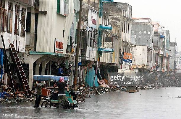 Indonesian men wade through a flooded street while salvaging their belongings from the derbis caused by tsunamis in Banda Aceh, 12 January 2005....
