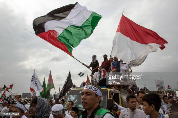 Indonesian men wave Palestinian and Indonesian flags at a large demonstration against the United States' decision to recognize Jerusalem as the...