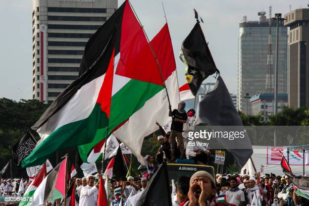 Indonesian men wave Palestinian flags at a large demonstration against the United States' decision to recognize Jerusalem as the Capital of Israel on...