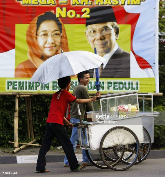 Indonesian men wheel food carts past an election poster of the incumbent President Megawati Sukarnoputri and her running mate Hasyim Muzadi downtown,...