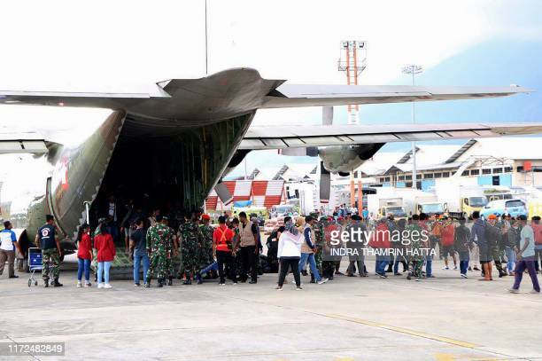 Indonesian military assist residents evacuated from Wamena as they arrive at an airport in Jayapura on September 30 after violence broke out again in...