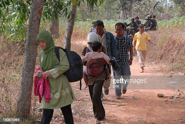 Indonesian Mobile Brigade policemen guard shiites Muslim as they are escorted to a safe area following attacks, in Sampang on August 27, 2012. Two...