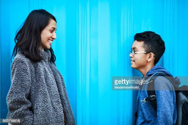 Indonesian mother and her 12 years old son talking and smiling