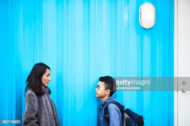 indonesian mother and her 12 years old son talking by the blue wall - 12 13 years stock pictures, royalty-free photos & images