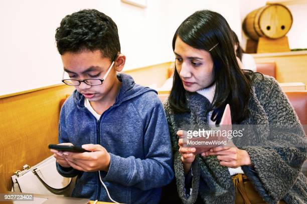 indonesian mother and her 12 years old son using their cell phones - 12 13 years stock pictures, royalty-free photos & images