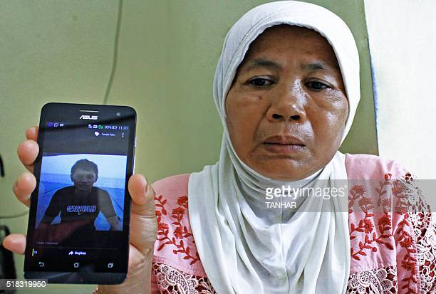 Indonesian mother Asmizar holds up a mobile phone showing a photograph of her son Wendy Rahadian one of the ten members of a tugboat crew who were...