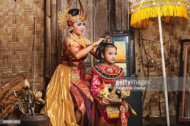 Indonesian Mother fixing the hair of her daughter