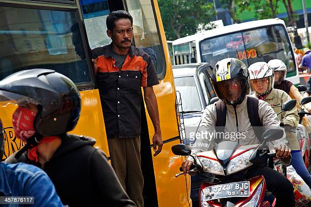 Indonesian motorcyclists drive past a bus in heavy traffic on December 19 2013 in Jakarta Indonesia Transportation experts have been warning that...