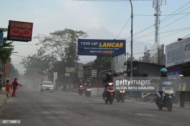 Indonesian motorists commute along an ash covered road after mount Merapi erupted in Sleman on May 11 2018 Indonesian villagers living in the shadow...